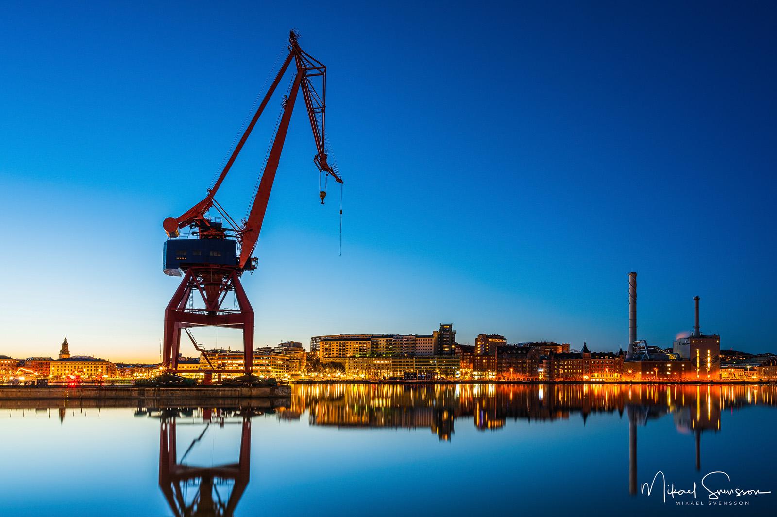Varvskran speglar sig i stilla älv. Göteborg.